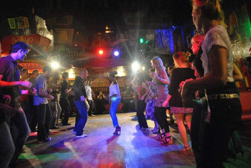 People dancing at a Paris salsa club during a meet-up with a local while traveling