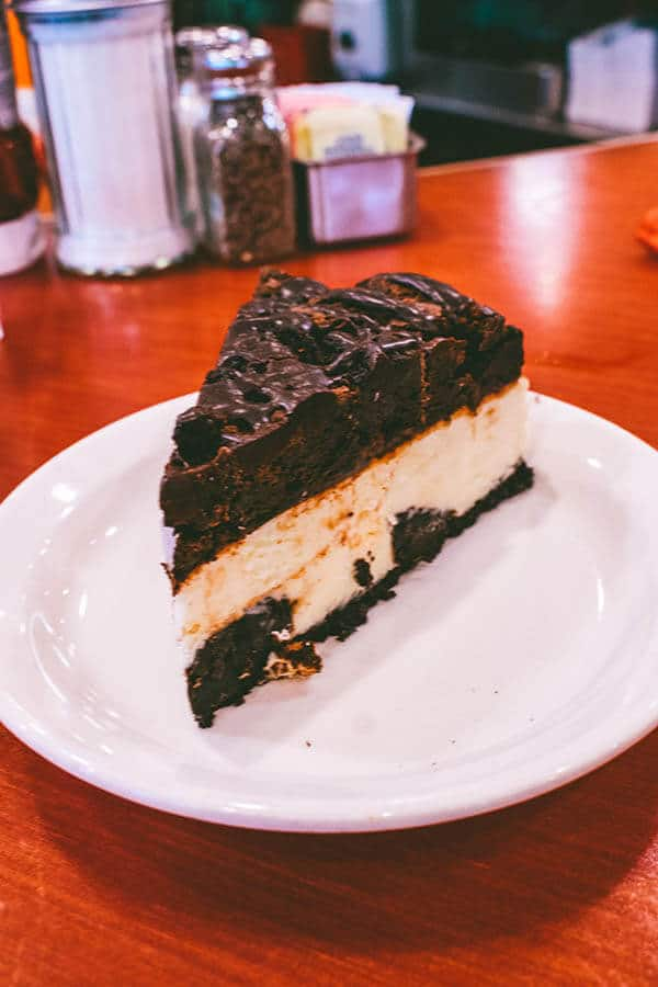 Slice of Brownie Explosion Cheesecake from Junior's, one of the most famous places to try New York style cheesecake in New York City!