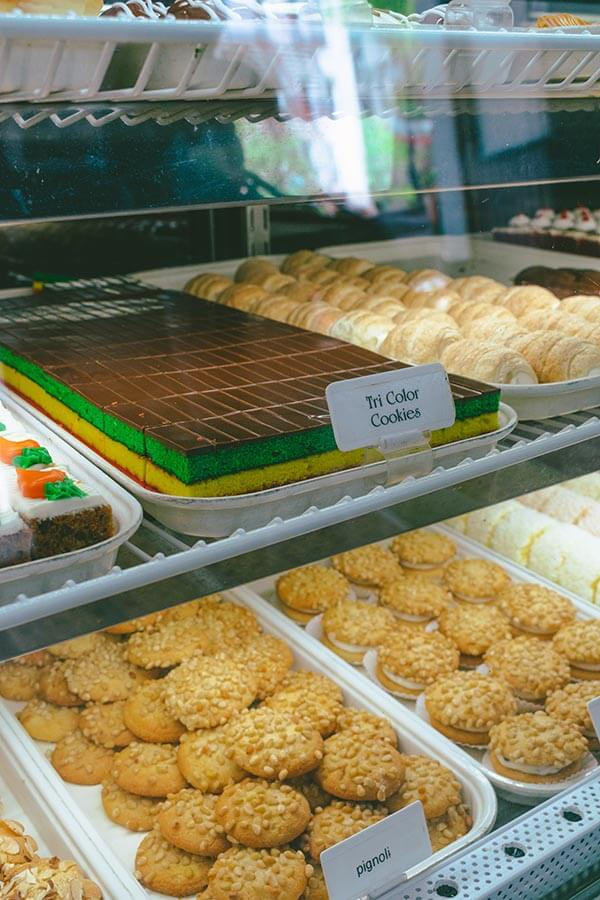 Pastry case with tricolor cookies and pignoli cookies at Artuso Pastry Shop in the Bronx, an institution in Belmont.