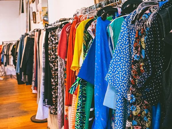 Racks of colorful dresses at Housing Works, one of the popular secondhand stores where you can shop for affordable clothes in New York City!