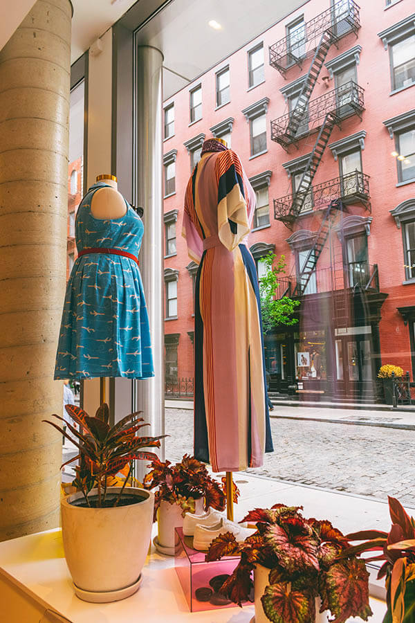 Colorful quirky patterned clothing in the window of the Modcloth Fitshop in SoHo with beautiful street in distance