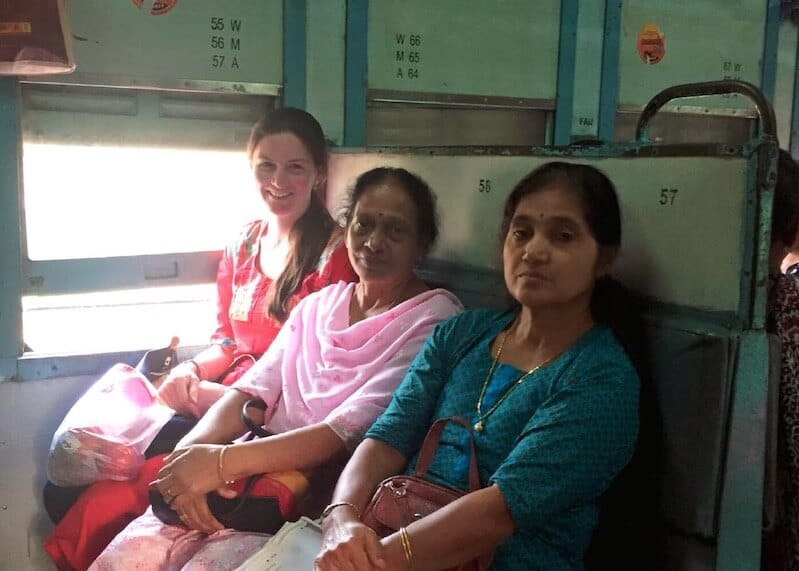 Woman with new local friends during a train trip, one of the ways to meet locals while traveling