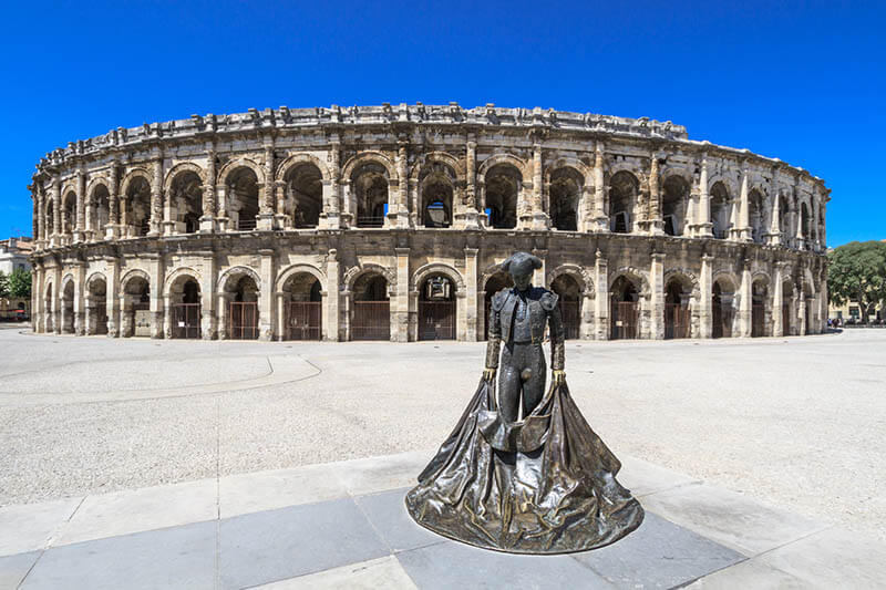 Bullfighter sculpture in front of the old Roman Arena in Nimes, France on a sunny day