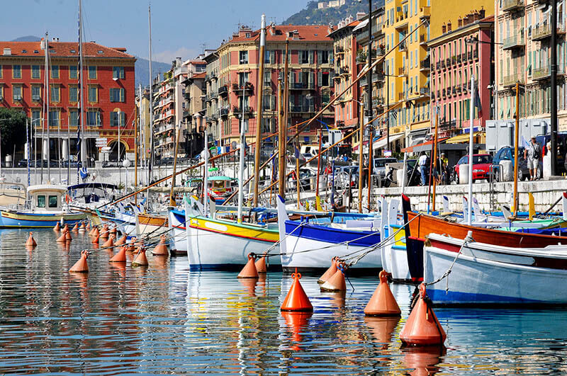 Colorful port of Nice, France with floating boats and reflection of houses in the water
