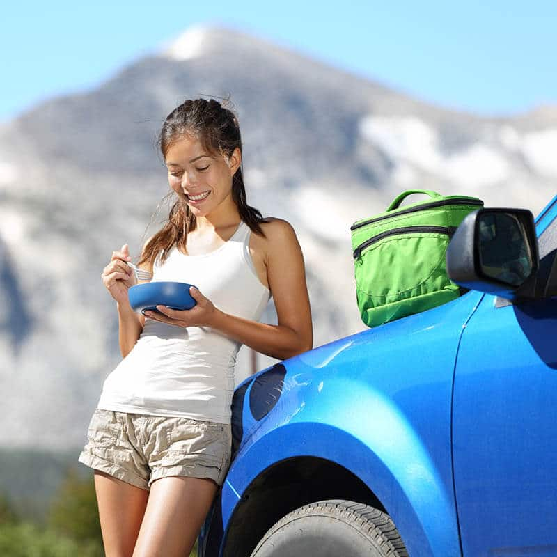 Woman eating snacks by car after purchasing snacks, one of the best tips for saving money on a USA road trip!
