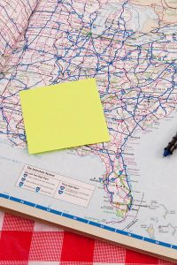 Person planning a first time road trip through the United States using an old school atlas with map of the United States open.