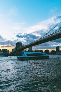 New York ferry sailing underneath the Brooklyn Bridge with stunning views of Manhattan at sunset