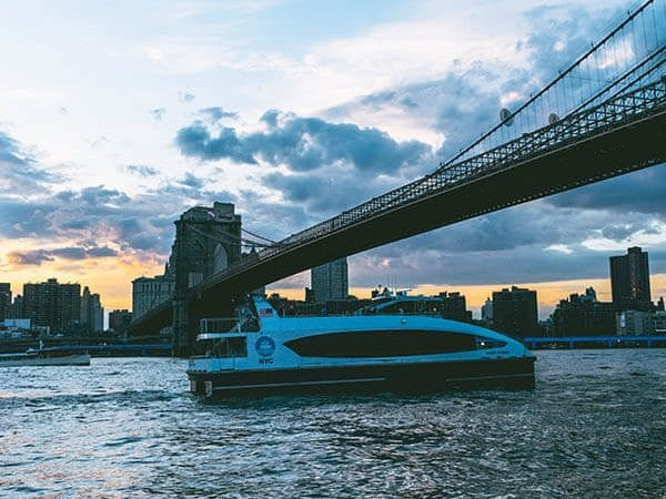 New York ferry sailing underneath the Brooklyn Bridge with stunning views of Manhattan at sunset