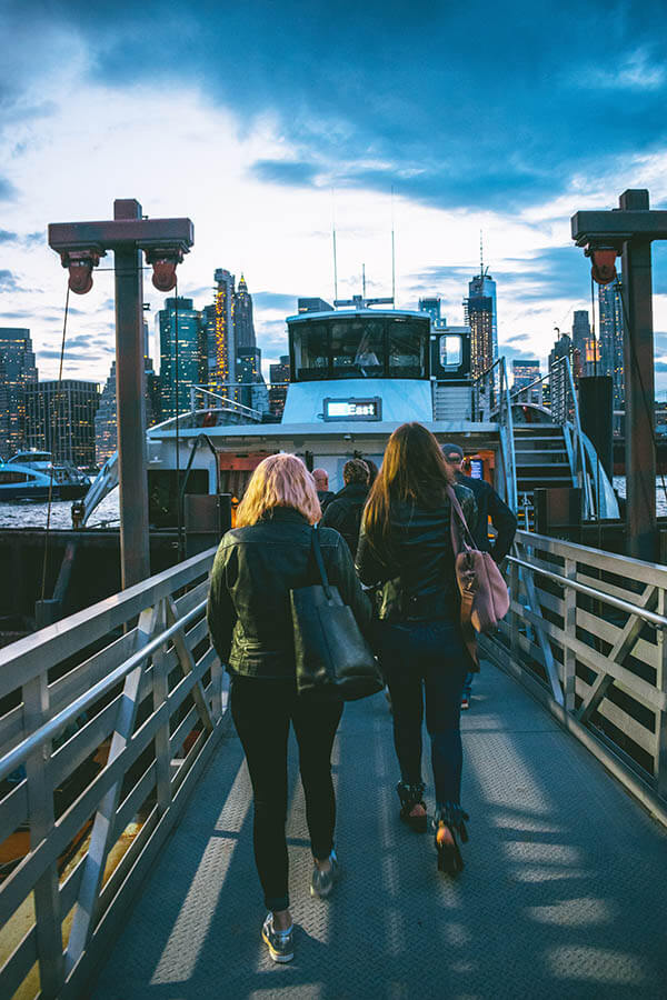 People boarding the New York City ferry from Brooklyn at sunset.