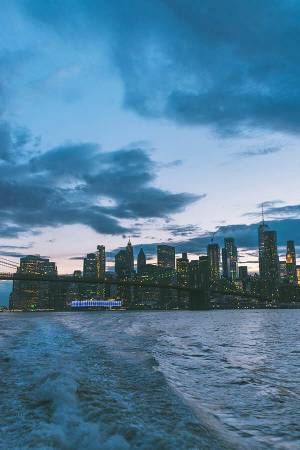 Beautiful view of Manhattan at dusk with sunset hues seen from the NYC ferry from Brooklyn