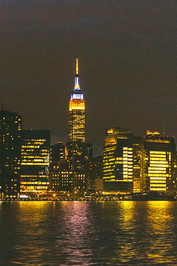 Empire State Building lit up at night seen from the New York City ferry