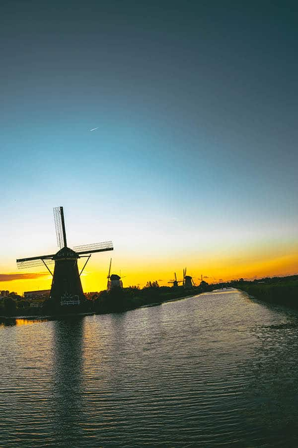 Beautiful sunset at Kinderdijk with orangey hues with windmills in shadow