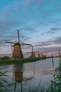 Beautiful pink and purple colors in sky with rows of windmills in Kinderdijk, the Netherlands