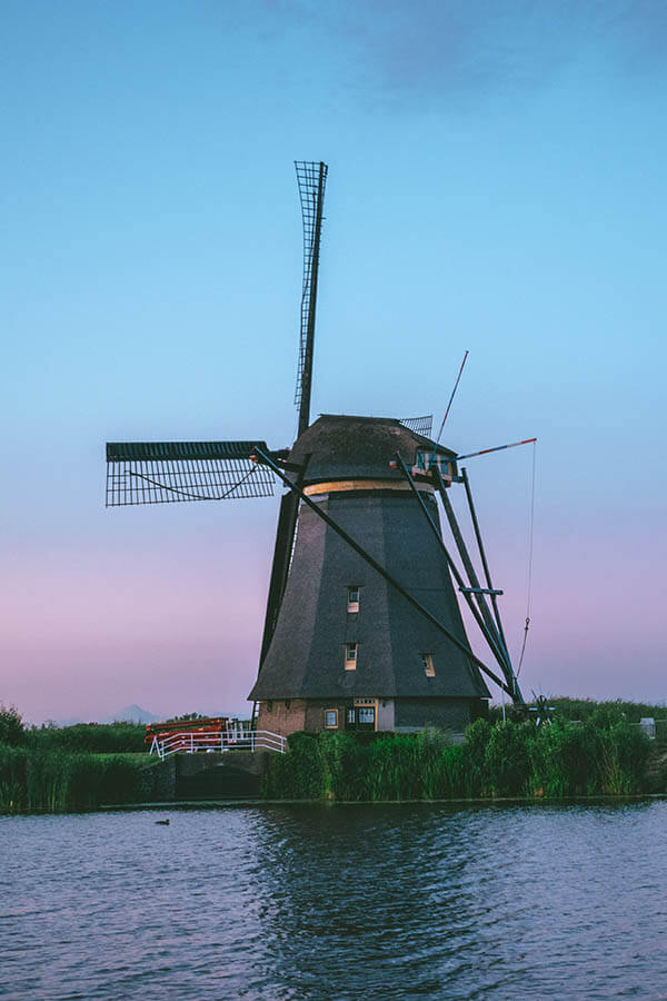 Beautiful Dutch windmill at sunset with blue and pink hues in background