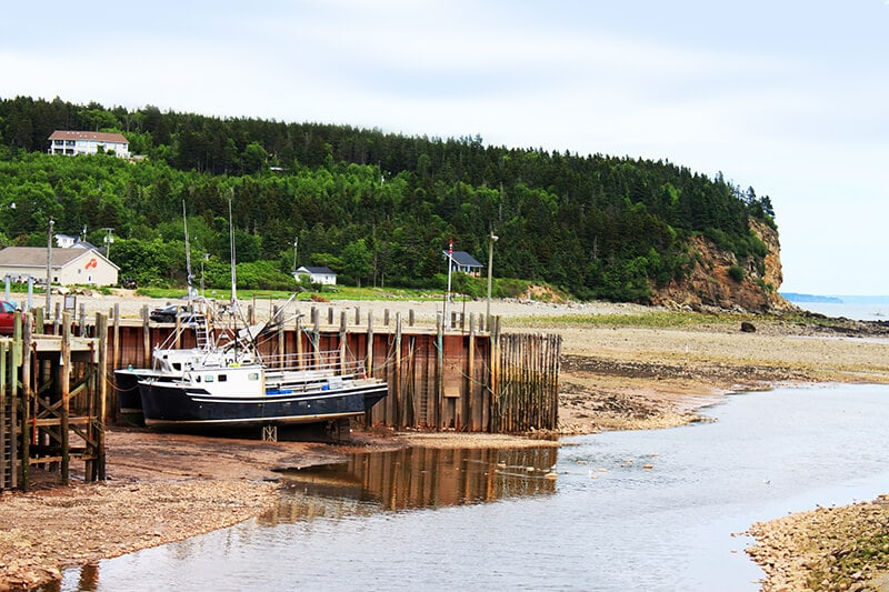 Beautiful boat and dock with cliffs behind seen in Alma, New Brunswick, Canada.