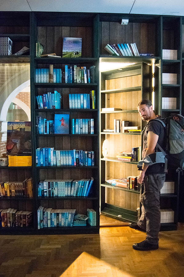 Man with entrance to hidden room within bookshelf at a unique hotel in Amsterdam called Hotel Not Hotel
