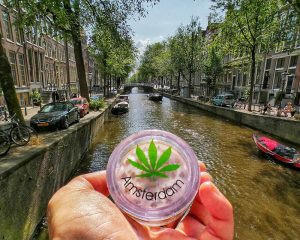 Amsterdam weed container with marijuana symbol with background of Amsterdam canals