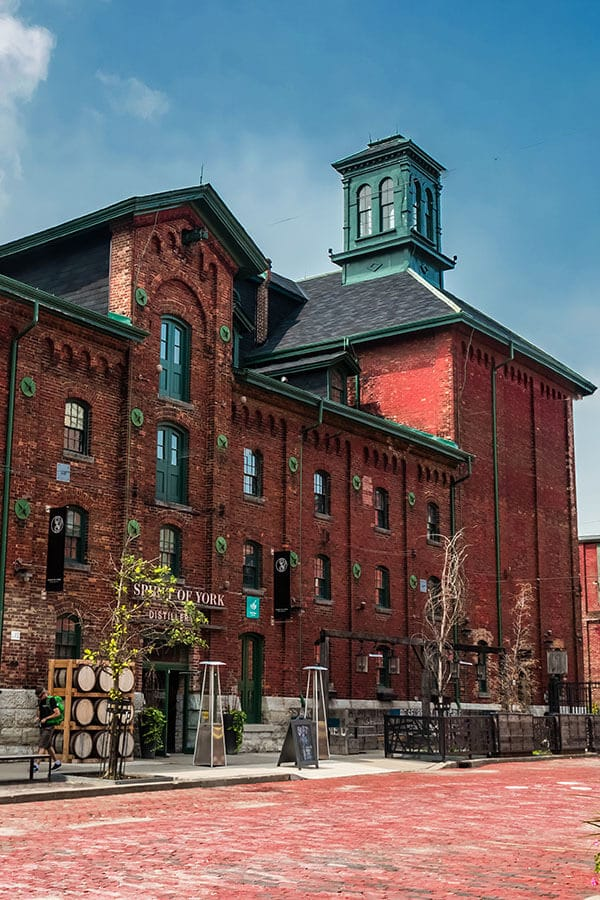 Stunning exterior with red bricks of the Distillery District in Toronto, Canada, one of the coolest parts of Toronto to visit!