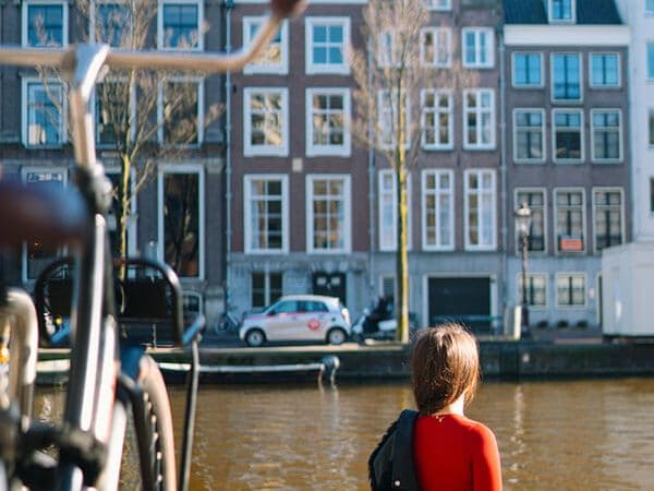 Girl enjoying solo travel in Amsterdam while sitting along Amsterdam canals!
