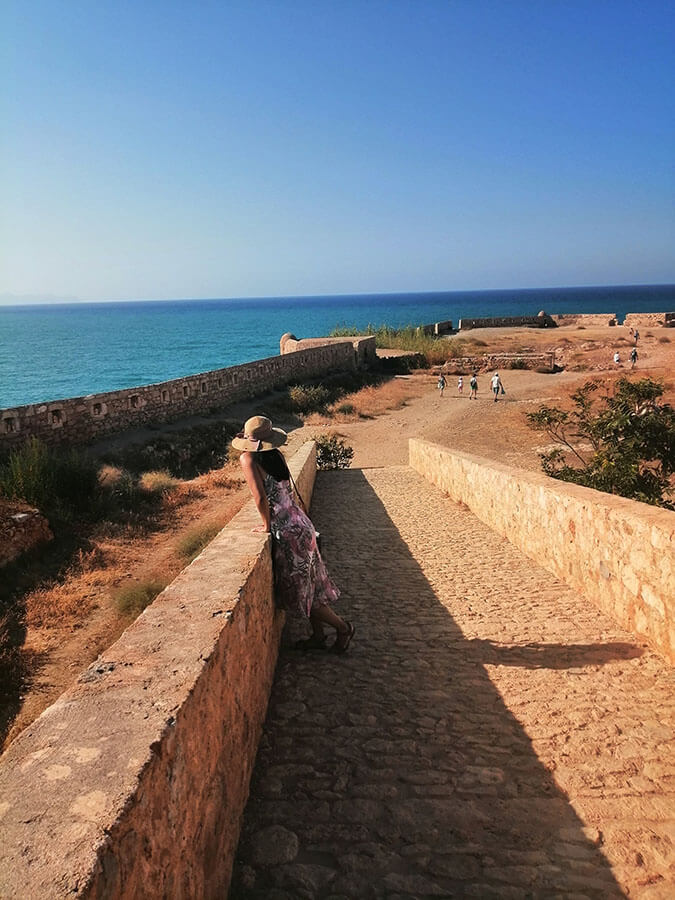 Girl enjoying the fortress in Rethymno, Crete with views of sea