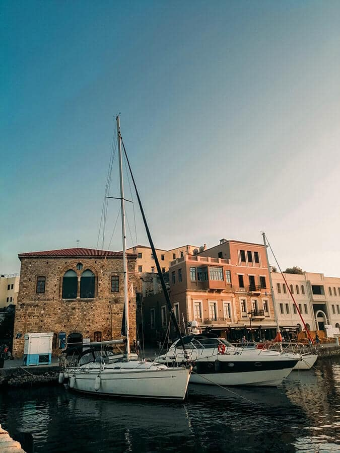 Beautiful golden hour with ships near port of Chania, Crete. One of the highlights of any Crete itinerary!