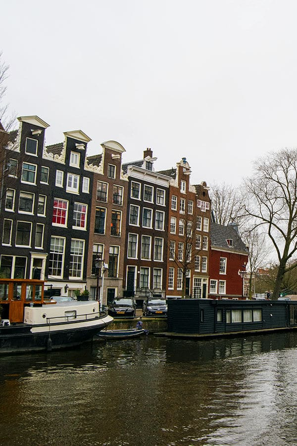 Beautiful canals of Amsterdam with a houseboat seen on a layover from Amsterdam.