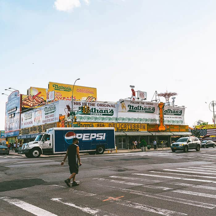 Man walking past the original Nathan's building on Surf. Avenue in Coney Island
