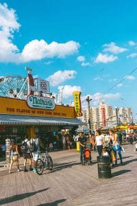 People walking on the Coney Island boardwalk past Nathan's Famous Hot Dogs in Brooklyn, New York