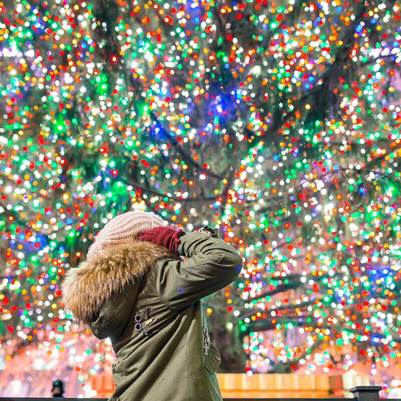 Woman enjoying Christmas Day in New York City, one of the best times to enjoy NYC!