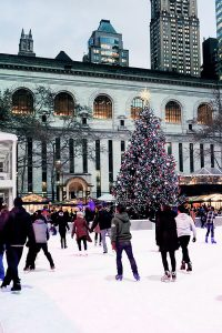 People enjoying ice skating in Bryant Park, one of New York's best Christmas markets and ice skating rinks during Christmas in New York!