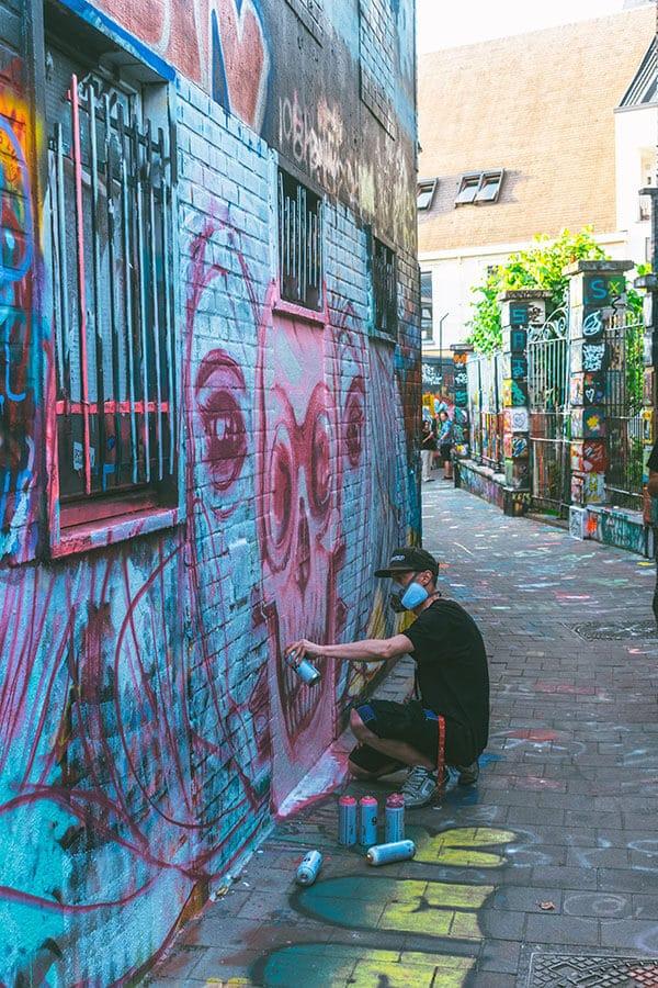 Man painting graffiti on Graffiti Street in Ghent, Belgium!