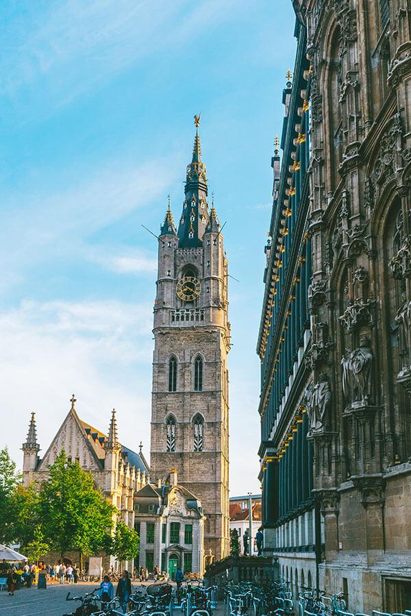 Beautiful Belfry of Ghent in Gent, Belgium.  This UNESCO recognized attraction in Belgium is set against a blue sky!