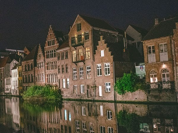 Beautiful former guild houses in Ghent, Belgium along the Leie River after sunset with reflection.