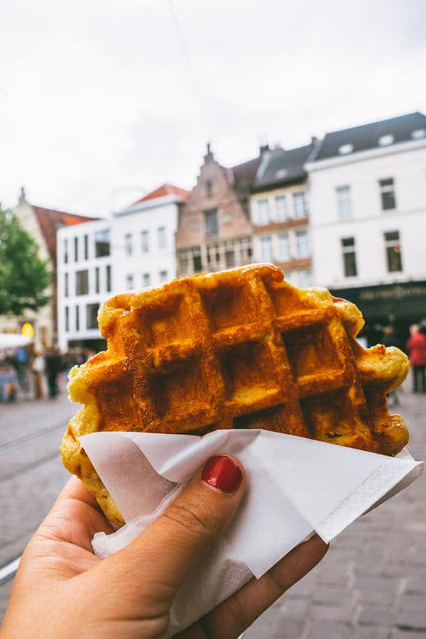 Belgian Luikse waffle in Ghent, Belgium with background of historic city center of Gent