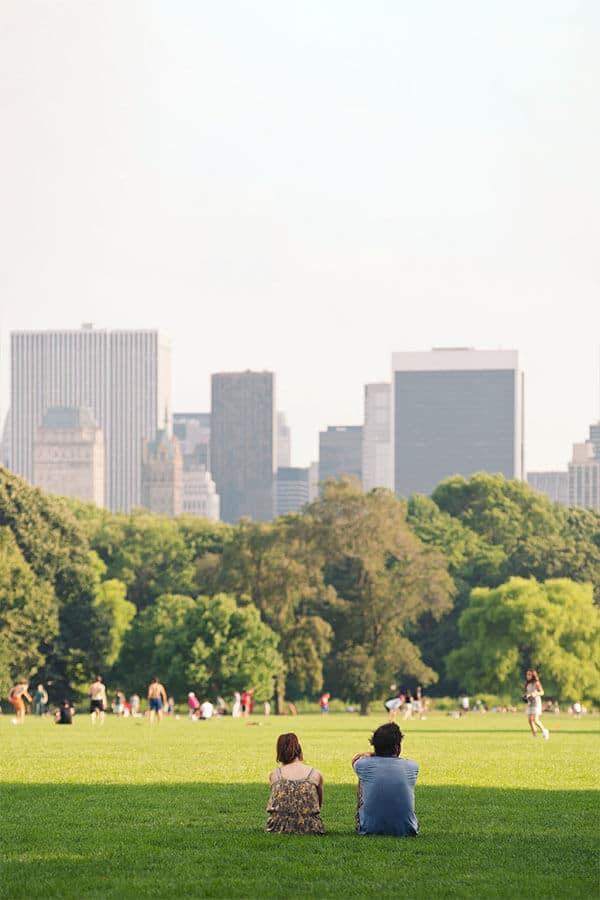 Couple enjoying views of New York City from Central Park. Explore this beautiful park in New York City as part of the best free things to do in New York City!