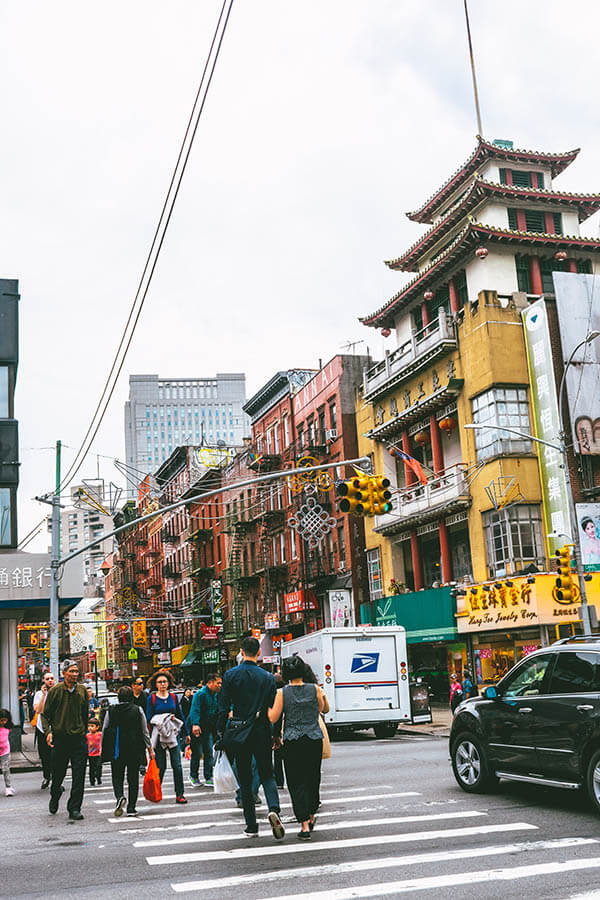 Couple walking down the street in Chinatown neighbourhood of New York City. Experience Chinatown like a local with these local tips!