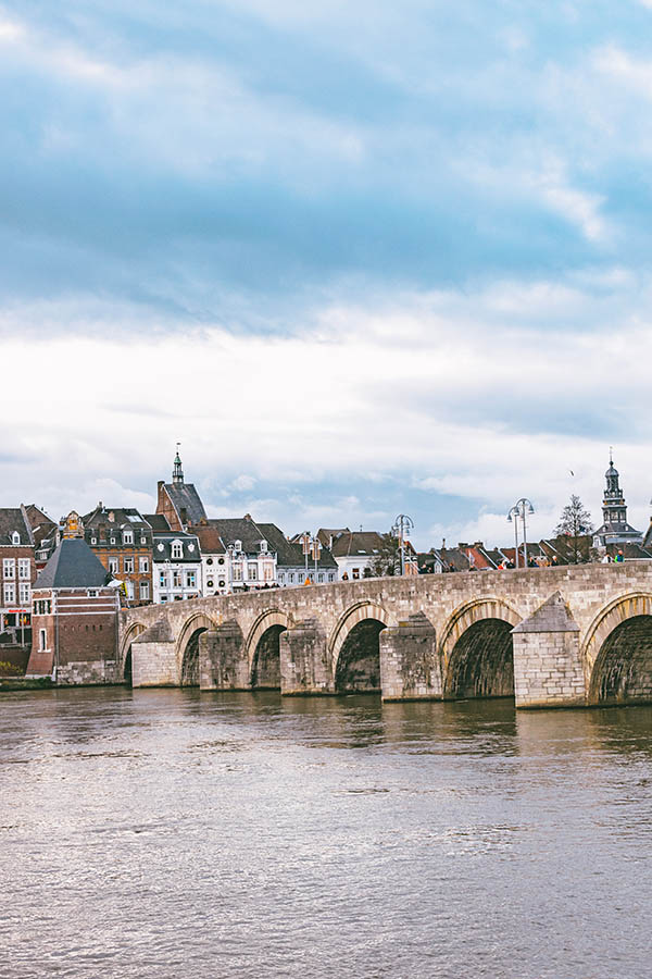 Beautiful view of the Maas river with bridge with Maastricht historic city center in the distance. Enjoy the river views is one of the best things to do in Maastricht