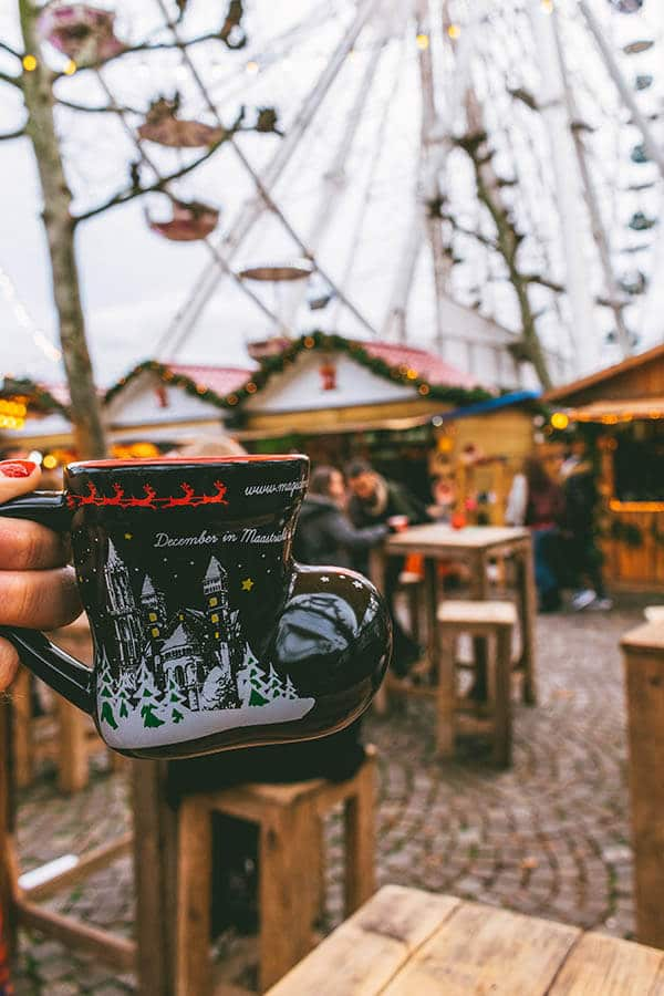 Girl holding cup of gluhwein with ferris wheel and Christmas markets stalls behind at the Magical Maastricht Christmas market in Maastricht, the Netherlands