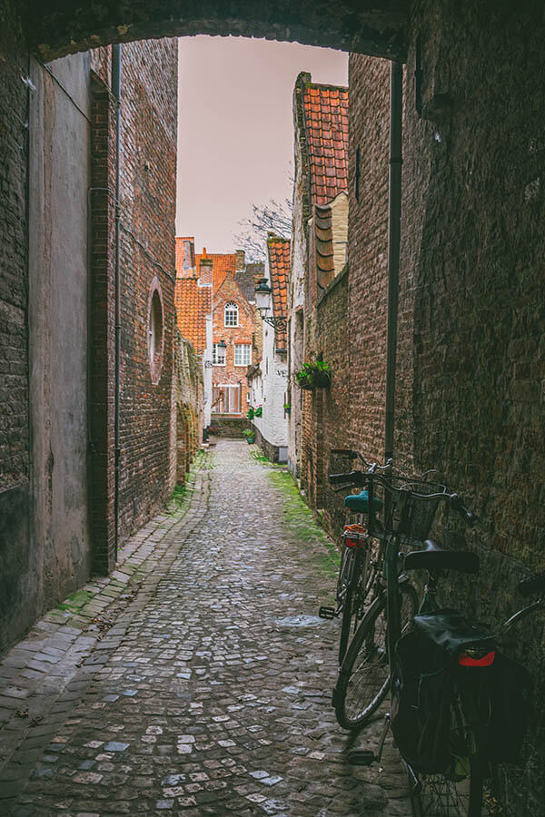 Beautiful secret alleyway leading to a historic almshouse in Bruges, Belgium.
