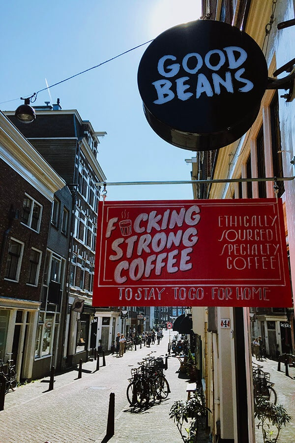 Sign outside of Good Beans coffee cafe in Amsterdam with street view, one of the best coffee places in Amsterdam!
